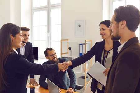 Female business partners making deal, shaking hands in negotiation meeting. Happy client thanking company manager for help. Smiling CEO welcoming new intern employee to company