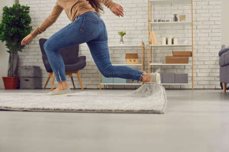 Unrecognizable person trips over rug at home. Clumsy faceless woman in uncomfortable shoes stumbles on rug in living-room and falls down on floor. Concept of getting injured in domestic accidents