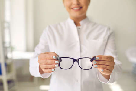 Happy optician asking you to try on these new good quality glasses. Cropped smiling doctor holding modern eyewear. Concept of optometry, eyeglasses prescription, taking care of eye health. Soft focus
