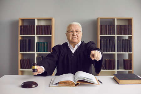 Angry judge finds the accused guilty, passes judgement and rules case closed. Strict old male judge hitting sound block with gavel, pointing finger at you and pronouncing sentence in court of law Stock Photo