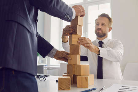 Mature and young businessmen making wood block tower as metaphor for building strong business together. Concepts of collaboration, succession, maintaining financial stability, economical growth