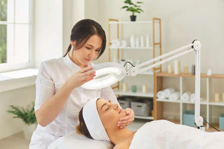 Woman dermatologist directing lamp to womans face during checking skin elasticity or making skin examination in beauty salon. Correction of facial wrinkles and skin tightening concept