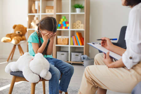 Children need help. Bullied little schoolgirl crying in psychologists office unable to control emotions, sharing problems and traumas. Professional psychotherapist talking to distressed bully victim