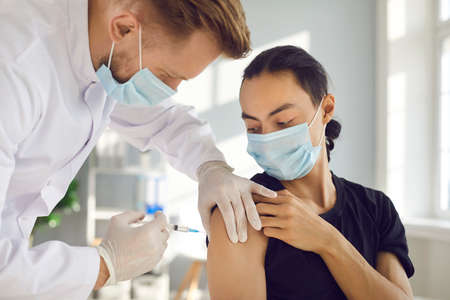 Young man in medical face mask getting flu shot during seasonal infection outbreak. Male doctor or nurse giving effective vaccine injection to patient during modern vaccination campaign