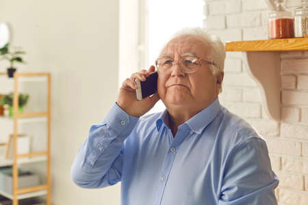 Older man talks on the phone standing in a bright living room and looks up thoughtfully and listens carefully to the interlocutor. Person tries to remember something or thinks what to say.