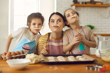 Happy family having fun while cooking. Little kids and young mother playing with cookie dough in the kitchen. Portrait of cheerful mom and cute children making funny faces with fake pastry mustaches