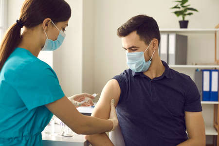 Professional nurse in medical face mask giving flu shot to male patient during seasonal vaccination campaign. Doctor injecting young man with influenza, AIDS or Covid-19 vaccine at clinic office