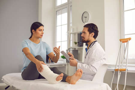 Physical injury treatment: Serious doctor listening to patient with bone fracture. Young woman with broken leg talking to traumatologist or orthopedic surgeon during medical exam in hospital or clinic