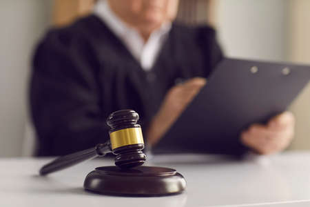 Close up of a dark brown judges gavel on the table against the background of a judge reading the verdict. Concept of justice, law, jurisprudence and court proceedings. Blurred background.