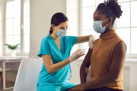 Young African American lady sitting at doctors office and getting modern Covid 19 shot. Nurse in medical face mask and gloves holding syringe and giving female patient flu vaccine injection in arm