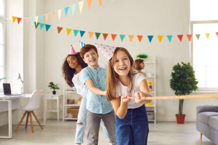 Childrens team in colored conical hats has fun and plays a game of tug of war at a festive childrens party in honor of the birthday. Multiethnic girls and boys celebrate together at home.