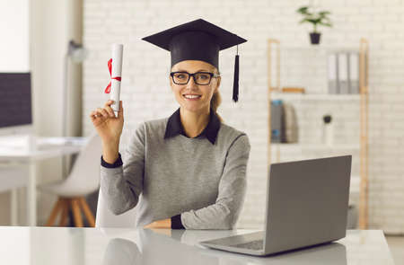 Portrait of talented online degree courses graduate holding diploma or certificate scroll. Smiling gifted student in mortar board and glasses sitting at desk with laptop computer and looking at camera