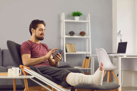 Male patient with broken leg in plaster cast relaxing at home. Happy man with bone fracture sitting in comfortable armchair, using mobile, texting friends, making phone calls, chatting on social media