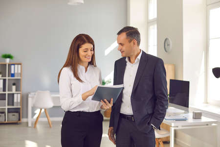 Business, office, communication, teamwork concept. Smiling man and woman business people office workers standing and discussing project or report details together over spacious modern workplace