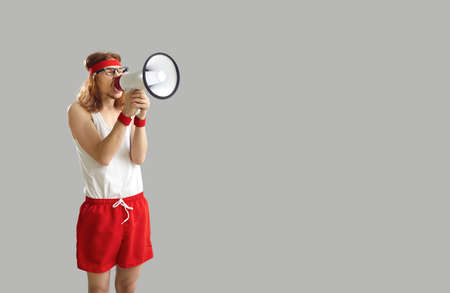 Funny noisy crazy man in sports shorts yelling in megaphone, announcing important marketing message, advertising workout wear and gym equipment sale, standing on grey empty space background