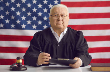 Man of law, justice and wisdom. Serious incorruptible old judge sitting at desk in courtroom during court hearing. Honest mature judge sitting at table in courthouse against American flag background