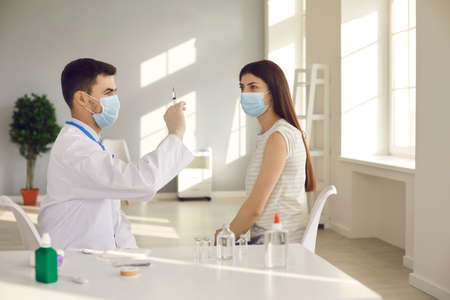 Immunization and vaccination campaign concept. Medical worker preparing flu or Covid-19 vaccine injection. Young woman in face mask sitting at table at hospital waiting for doctor to get syringe ready