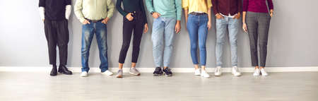 Your shoes says a lot about you. Cropped image of the legs of people in ordinary clothes and shoes standing in a row near the wall. Concept of diverse people in modern business. 免版税图像