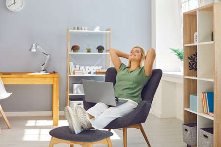 Young woman sitting on chairs in comfortable position in office with laptop and relaxing feeling happy with eyes closed. Freelance, distant working, online communication concept 免版税图像