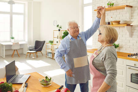 Love never grows old. Happy senior woman dancing with mature loving husband in the kitchen while cooking dinner. Old married couple having fun together at home in the kitchen enjoying cooking.