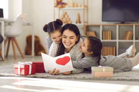 We love you. Smiling young woman getting presents from kids. Two cute twin daughters giving mom handmade greeting card. Little children lying on floor, hugging mommy and wishing her Happy Mothers Day