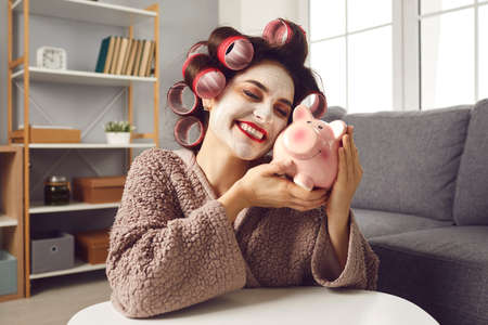 Happy funny young woman with beauty face mask on, in hair rollers and bathrobe, hugging pink piggy bank, smiling and daydreaming. Concept of loving money, making plans, and family budget management