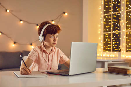 Red haired boy in headphones sitting, watching lesson or course online on laptop and making notes at home with decorated room. Distant education, elearning, online lesson and course concept
