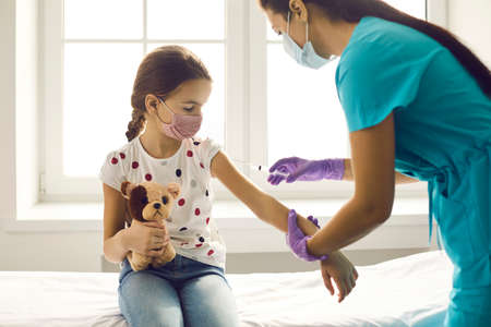 Concept of immunization for children. Nurse injecting little kid with Covid-19 vaccine. Brave girl in medical face mask looking at needle in doctors hands while getting flu shot at clinic or hospital