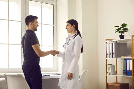 Trust concept. Happy doctor and male patient smiling and shaking hands before medical interview at office of modern clinic. Young man getting acquainted with friendly female physician at the hospital Stockfoto