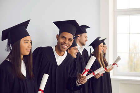 Confident in future. Smiling African-American exchange program student in black graduation cap and gown holding university diploma and looking at camera, standing together with international graduates