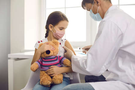 Immunization for children concept. Brave kid getting flu shot at doctors office, holding teddy bear toy and looking at needle. Medical specialist injecting child with vaccine at clinic or hospital