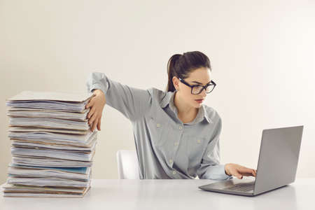 Young accountant working on laptop computer sitting at desk with pile of papers. Paperwork vs electronic documents. Storing files in digital database. Having quick convenient access to storage system Stock Photo