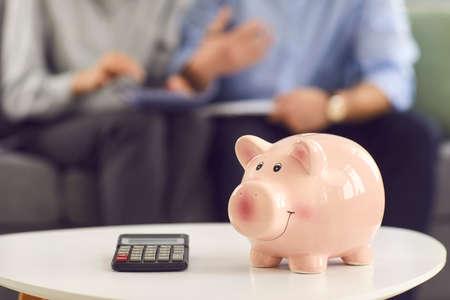 Calculator and pink piggy bank on table up close, couple managing family budget in blurred copy space background. Concept of people and finance, saving up money, paying taxes and planning expenses