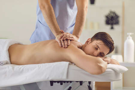 Young relaxed man with eyes closed enjoying procedure of medical massage of back and shoulders from professional masseur doctor. Back massage treatment in medical clinic from professional masseur Stock Photo