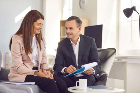 Adult male manager showing his female colleague a tablet folder with recorded business ideas while sitting in the office during a coffee break. Concept of teamwork and exchange of views at work.