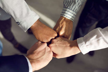 Team of young mixed race business men and women in formal office suits joining hands ready to collaborate, close-up. Concept of colleagues, coworkers, support, teamwork, working together, unity, power