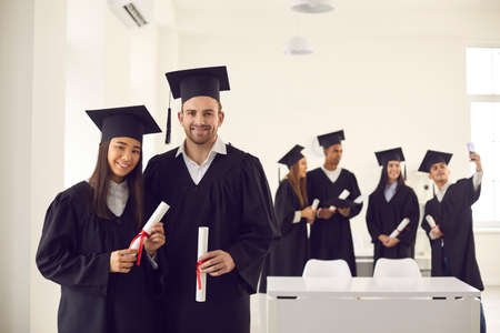 Smiling couple classmates asian girl and caucasian boy students university graduates in mantles standing with dimplomas over friends making selfie at background. Graduation from university concept