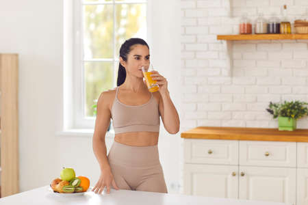 Morning routine. Beautiful fitness woman in sportswear drinks fresh fruit juice after workout standing at home in the kitchen. Concept of a healthy diet and vitamins. 免版税图像