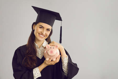 Saving money to pay for college or university education concept. Happy smiling female student in gown and mortarboard holding piggy bank and looking at camera isolated on gray blank space background