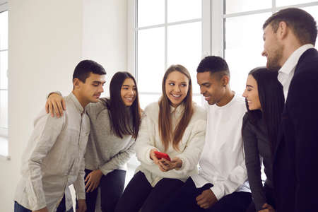 Group of young cheerful different ethnicity people team or students classmates sitting on windowsill and looking on girls smartphone having fun together. International team, multi ethnic group concept
