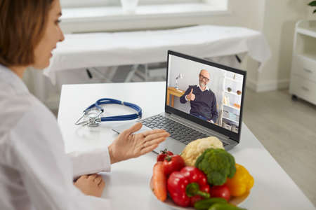 Video call wellness consultation: Online dietitian or nutritionist sitting at laptop and talking to happy smiling satisfied elderly client whos giving thumbs-up, thanking doctor for healthy diet plan 免版税图像