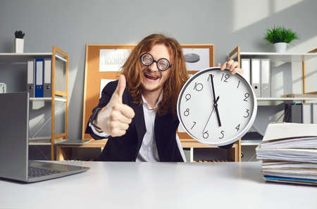 Happy funny punctual young corporate employee sitting at office desk with laptop computer, holding clock that says its 5 pm and giving thumbs up excited its time to go home. End of work day concept