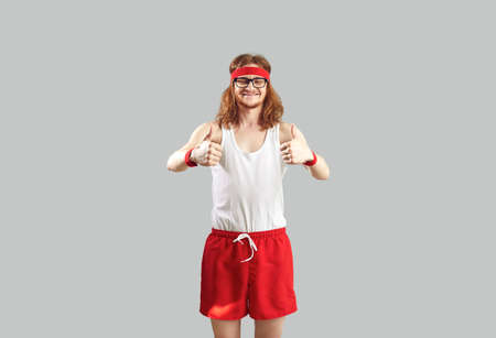 Funny smiling hipster young sportive man in red and white sportswear standing and showing thumbs up sings with fingers over light grey wall background. Funny active sport lifestyle of man concept 免版税图像