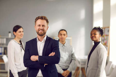 Portrait of a confident young business leader with a team of employees in the background. Man in a business suit with his arms crossed looks at the camera and smiles. Blurred background.