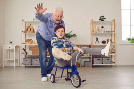 Active senior man feels young again when plays carefree childish games with grandson. Happy little kid having fun, riding tricycle and fooling around while enjoying free time with grandpa at home