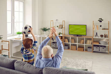 People sitting on sofa at home and enjoying final football match on TV. Granddad and grandchild supporting favorite team while watching soccer on big television set in Scandinavian style living-room 免版税图像