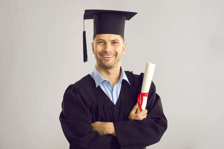 Studio portrait of satisfied student with his graduation certificate. Happy academy, college or university graduate standing against gray background, holding his diploma scroll and smiling at camera