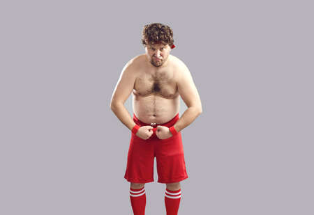Funny strong plump athlete in red gym shorts showing his chubby body standing isolated on gray background. Young man with curly hair and some belly fat flexing arms pretending to be tough guy