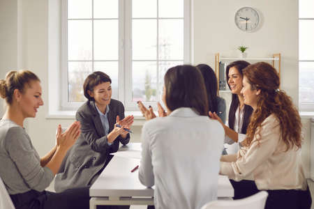 Group of smiling employees clapping hands in work meeting, approving of new corporate strategy. Team of happy business women sitting around office table, celebrating success and applauding each other