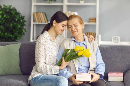享受在母亲或国际妇女的日的愉快的资深妇女礼物。爱年轻女儿给老妈妈花和礼物。坐有祖母和拥抱她的沙发的微笑的孙女
